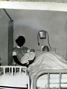 African American Female Nurse Holding White Doll White Male Mannequin In Bed