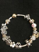 Authentic Pandora Gold And Silver Bracelet With 24 Charms Some Are Retired.