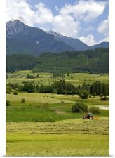 Poster Print Wall Art entitled A tractor harvesting a hay field on a farm at