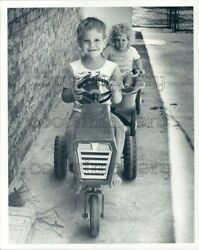 1983 Cute Boy Pedaling Toy Tractor Pulls Girl in Wagon Press Photo $20.00