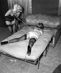 Bettie Page Woman in Black Lingerie and Leather Gloves is Pulling String while a