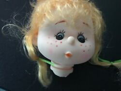 Doll head with curly blonde hair she has a button noise and freckles