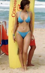 CATHERINE BELL IN A BLUE BIKINI AND A SURF BOARD. $1.50