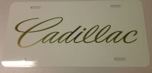 Cadillac Logo In Chrome Gold Vinyl On A White Aluminum License Plate Tag