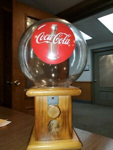 Vintage Coca-Cola gumball machine with wooden base