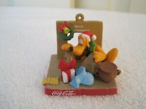 Disney – Pluto by fireplace w toys Coca Cola xmas ornament  - $29.95