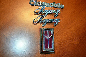 Oldsmobile Regency Emblems Badges Trunk Lock Cover 80s Oem