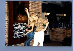 FOUND COLOR PHOTO U+8297 PRETTY WOMAN POSED WITH MAN BY JACK DANIELS SIGN
