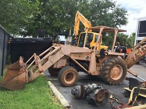 Massey Ferguson Tractor With Backhoe Outriggers digging Buckets